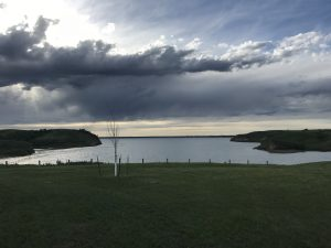 Lake Sakakawea in twilight, thunderclouds overhead, last light glimmering on the water